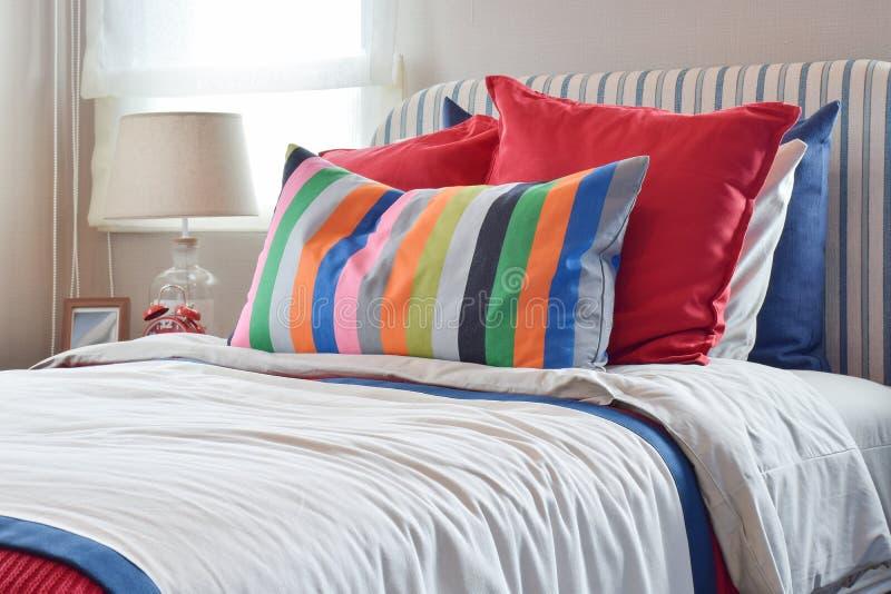 与Colourfull枕头和镶边枕头的镶边床头板在白色床上 库存照片