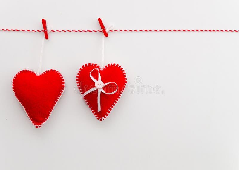 与copyspace的顶视图愉快的情人节概念在白色背景 垂悬在绳索的两红色感觉的枕头心脏 免版税库存图片