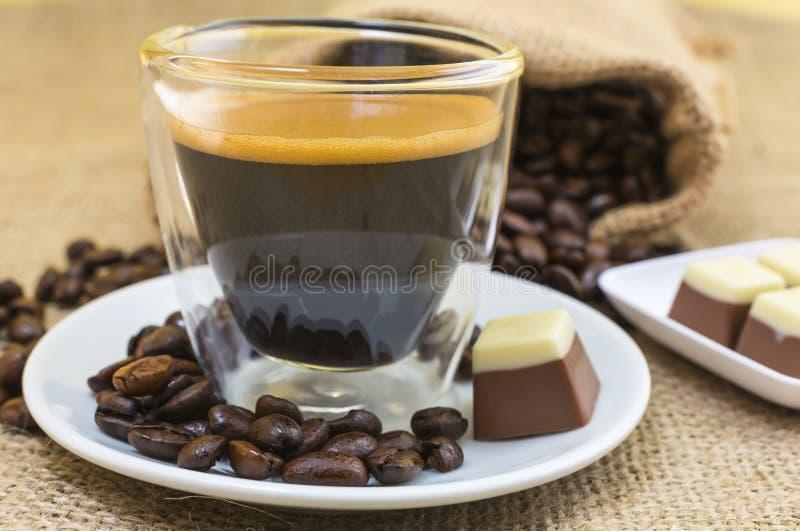 与crema的新鲜的浓咖啡在板材的咖啡和果仁糖 免版税图库摄影