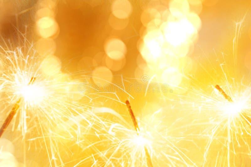 与de的金轻的闪烁发光物被聚焦的bokeh弄脏了背景 图库摄影