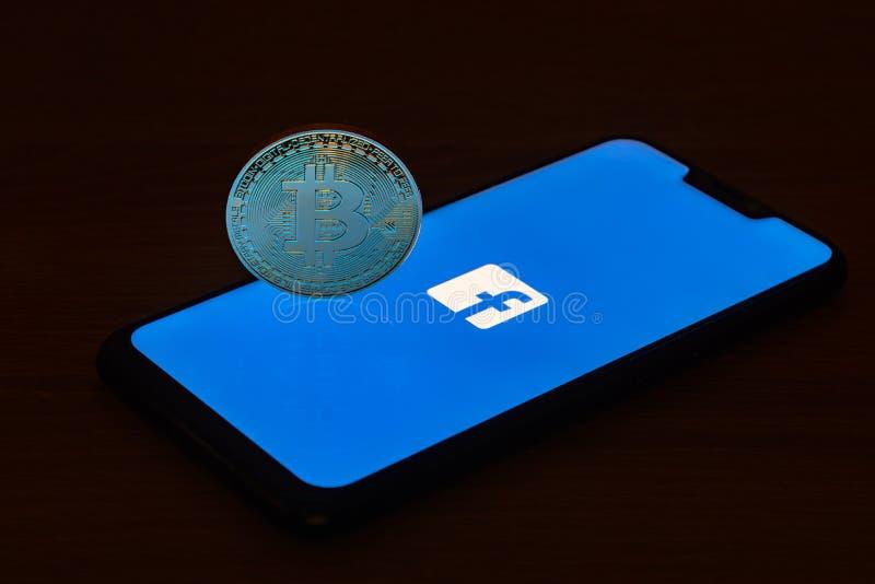 与Facebook商标的Bitcoin硬币在智能手机屏幕上 免版税库存图片