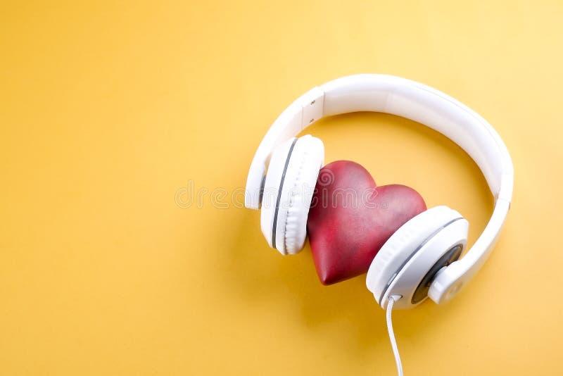 与hite耳机的世界音乐天主题的构成在黄色背景 免版税库存图片