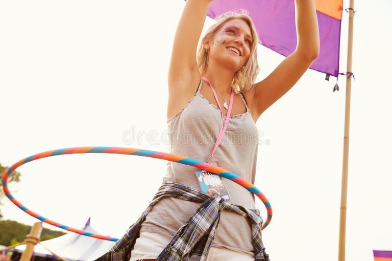 与hula箍的白肤金发的妇女跳舞在音乐节 图库摄影