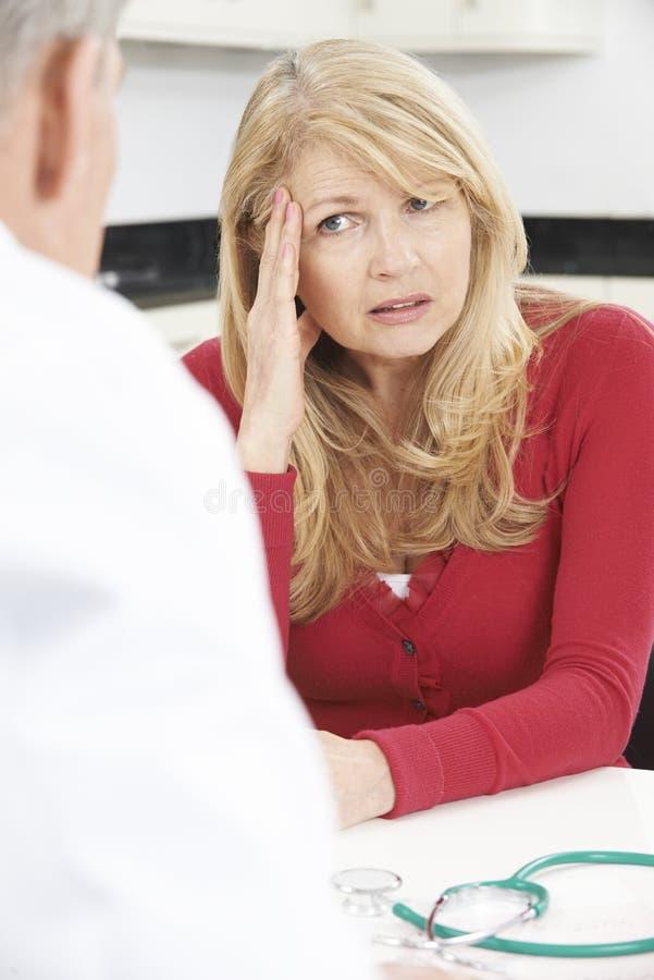 与In Surgery医生的担心的成熟妇女会谈 免版税库存照片