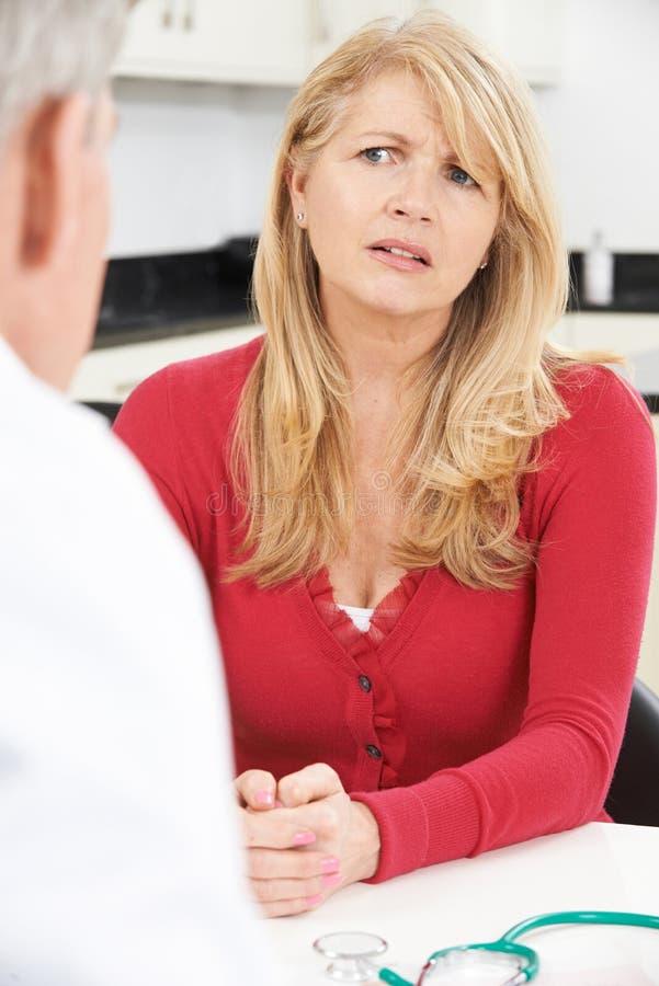 与In Surgery医生的担心的成熟妇女会谈 免版税库存图片