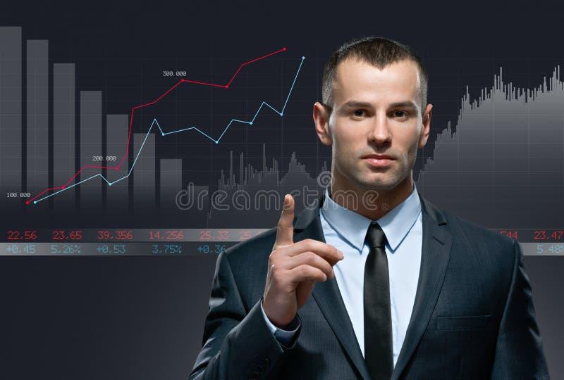 与infochart的年轻商人在黑背景 免版税库存照片