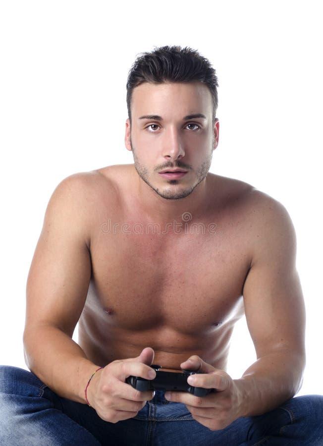 与joypad的英俊的年轻人赤裸上身的使用的计算机游戏 图库摄影