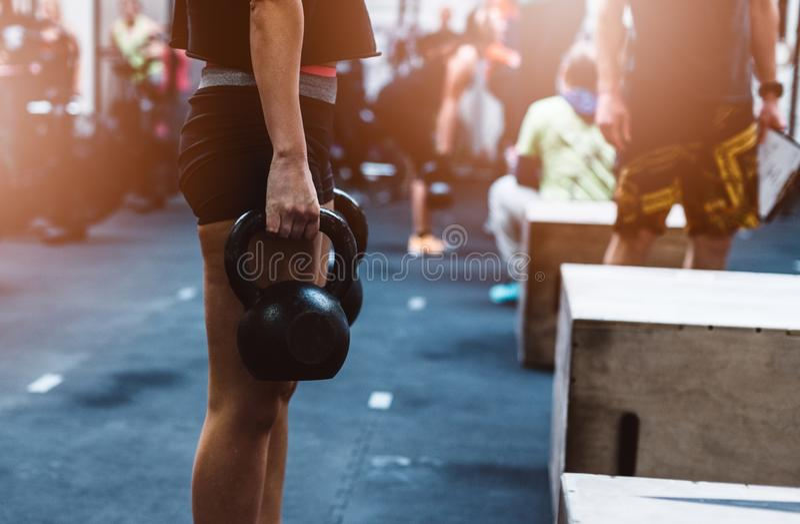 与kettlebell的少妇训练在功能健身健身房 库存照片