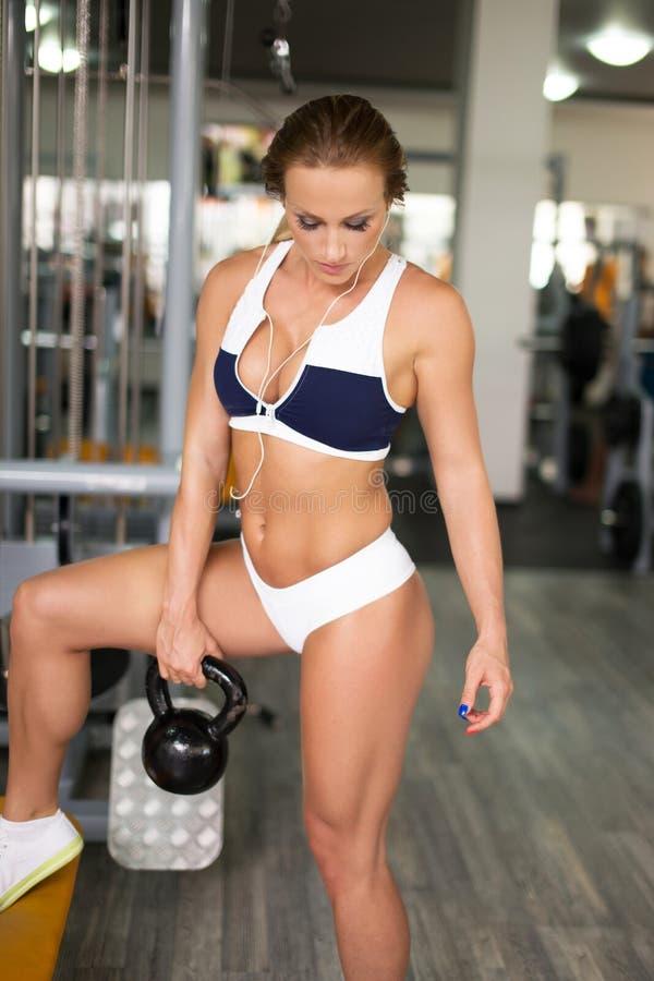 与kettlebell的年轻人适合的妇女锻炼在健身房 图库摄影