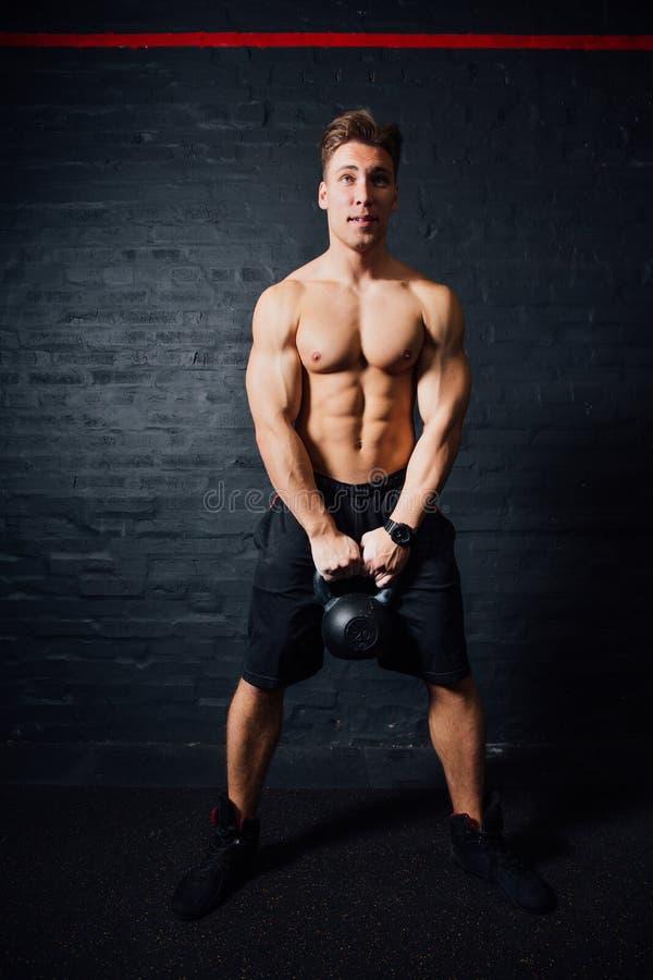 与kettlebells的年轻肌肉人训练 有赤裸躯干的人在黑暗的背景 免版税图库摄影