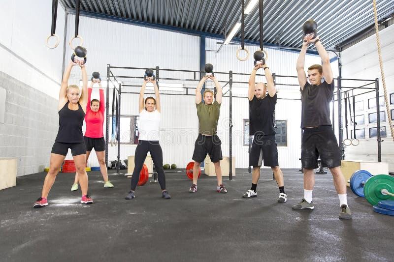 与kettlebells的队锻炼在健身健身房 库存照片