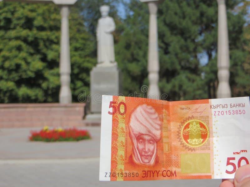 与Kurmanjan Datka的吉尔吉斯钞票在她的纪念碑背景在比什凯克 免版税库存图片