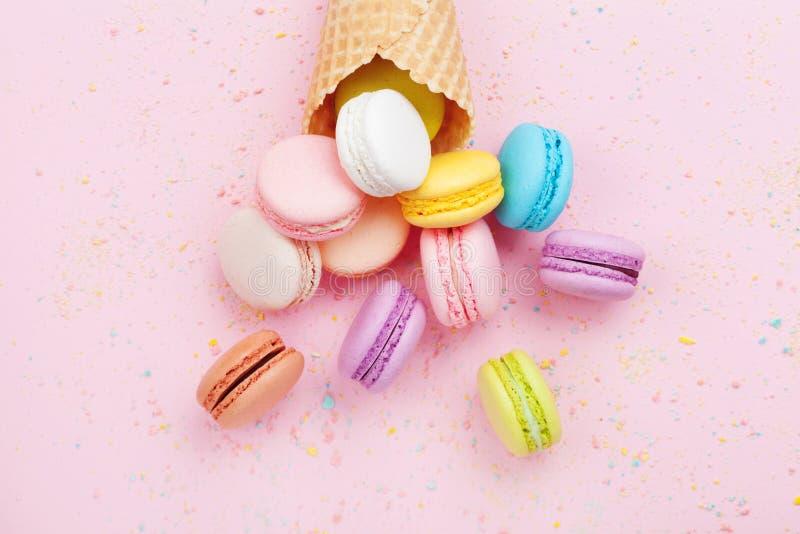 与macaron的甜奶蛋烘饼在桃红色淡色背景顶视图的锥体或蛋白杏仁饼干 平的位置构成 库存照片