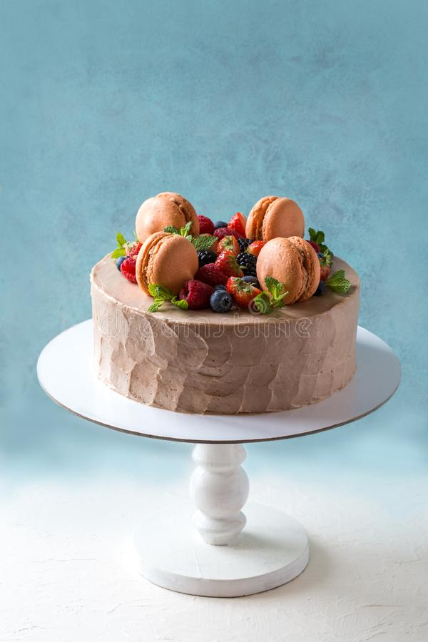 与macaron的自创蛋糕和新鲜水果,在蓝色背景的莓果 库存图片