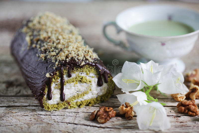与matcha茶和巧克力结冰的卷蛋糕用奶油填装了 库存图片