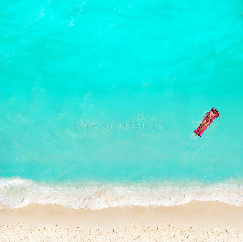 与matrass的女子游泳在海滩的水中 免版税库存照片
