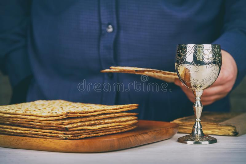 与matzah一块白色板材的红色洁净酒或matza和逾越节哈加达在作为逾越节被提出的葡萄酒木背景 免版税库存照片