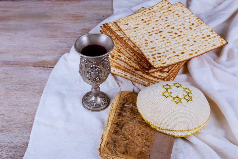 与matzah一块白色板材的红色洁净酒或matza和逾越节哈加达在作为逾越节被提出的葡萄酒木背景 库存图片