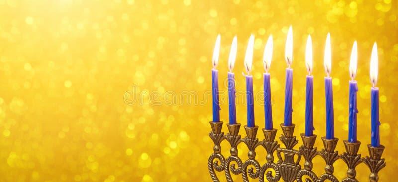 与menorah的犹太假日光明节网站横幅在金黄bokeh的设计和蜡烛 图库摄影