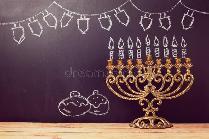 与menorah的犹太假日光明节背景在黑板用手速写了标志 免版税库存图片