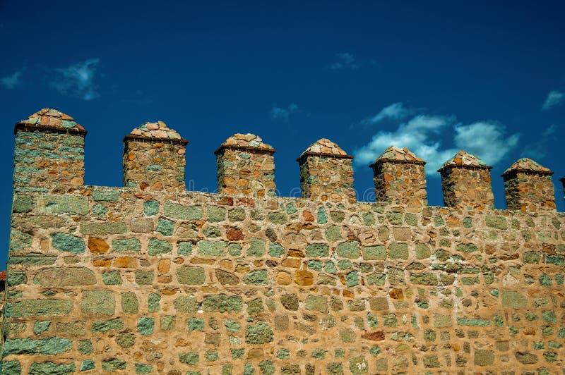 与merlons的城垛和垛口在石墙在阿维拉 免版税库存照片