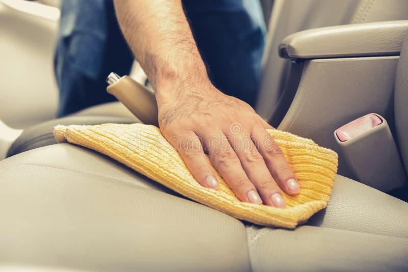 与microfiber布料的一个人清洁皮革汽车座位 免版税库存照片