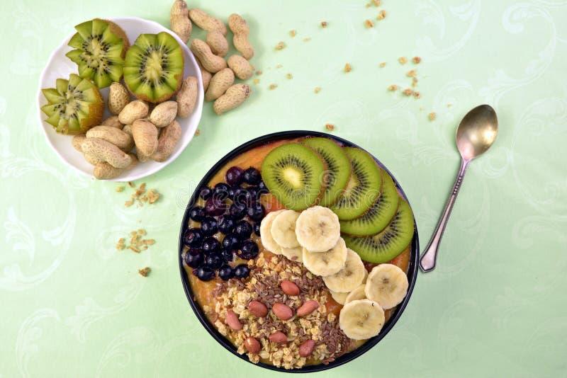 与muesli、acai蓝莓圆滑的人和猕猴桃,香蕉的早餐 免版税库存照片