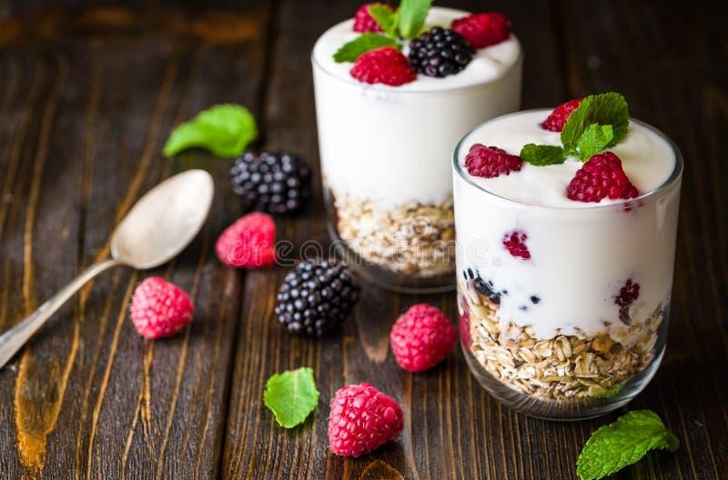 与muesli的白色在玻璃碗的酸奶和莓在土气木背景 免版税库存照片