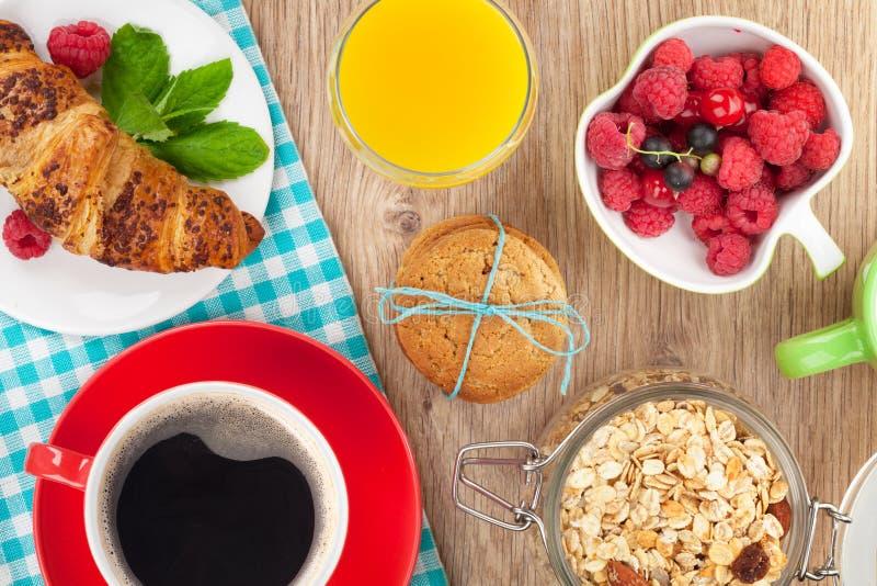 与muesli,莓果,橙汁,咖啡的健康早餐和 库存照片