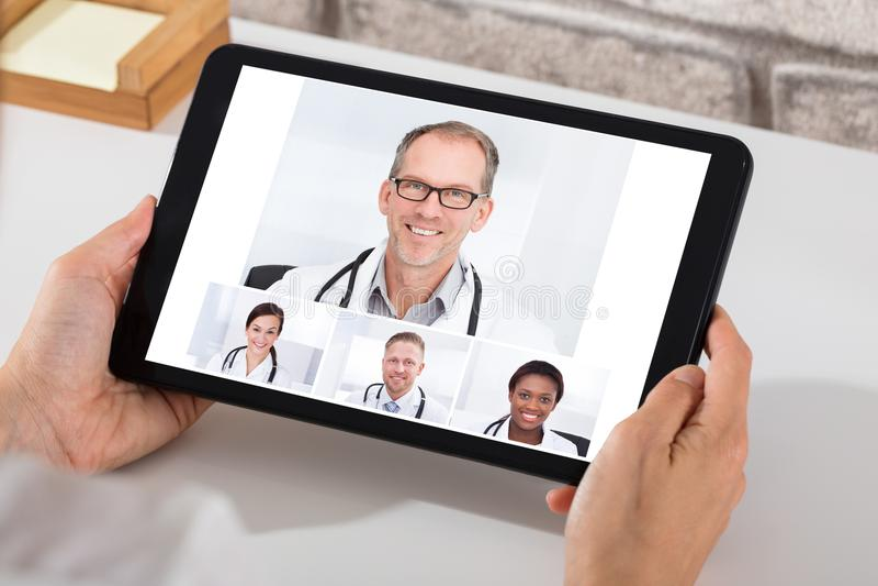 与On Digital Tablet医生的人电视电话会议 免版税库存照片