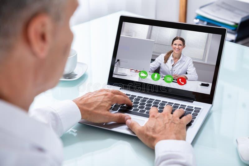 与On Laptop医生的商人电视电话会议 免版税图库摄影