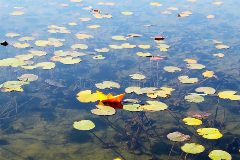 与origami小船的美好的风景 纸小船在有百合的一个池塘在百合的水和反射 免版税图库摄影
