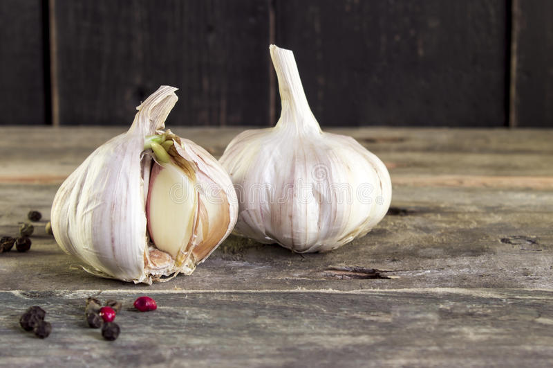 与papper的发芽的大蒜在一张土气木桌上 Springtim 免版税库存照片