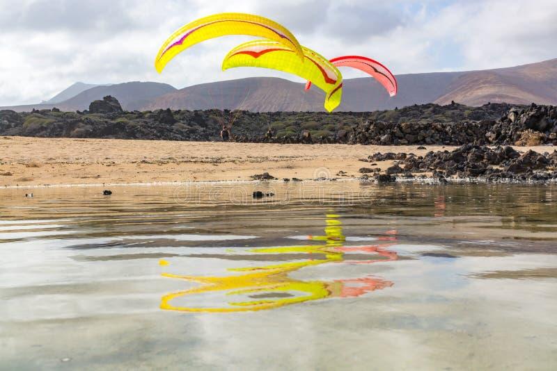与paraplanes在沙滩,极端体育的Paraplaners 免版税库存照片