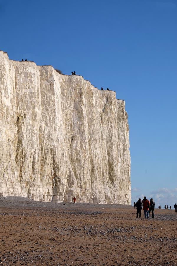 与Pebble海滩的白色白垩峭壁走在t的面孔和人们 免版税库存图片