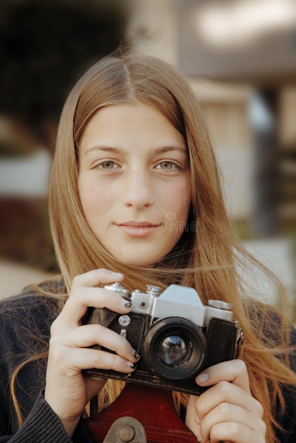 与phot影片照相机的年轻美丽的女孩画象 免版税库存图片
