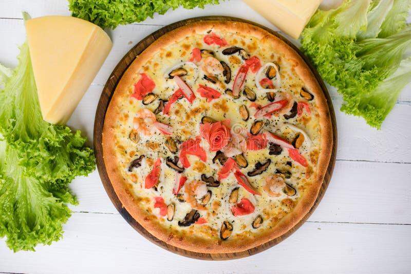 与seefood螃蟹的可口新鲜的比萨和淡菜和乳酪在蔬菜沙拉和乳酪围拢的白色木桌上 免版税库存照片