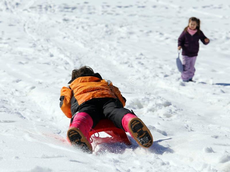 与sledging的儿童游戏在雪的冬天 免版税库存图片