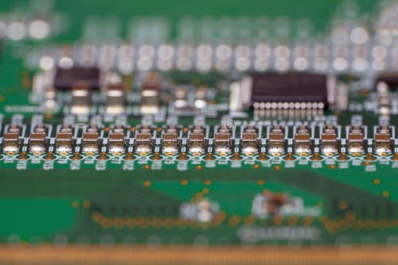 与SMD电容器特写镜头的PCB 译码器盘区tft LCD显示器的片段的宏观摄影 免版税库存照片