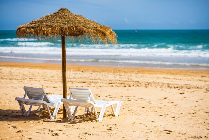 与sunbeds和伞的一个惊人的海海洋风景在波尔蒂芒,葡萄牙 阿尔加威地区 免版税库存图片