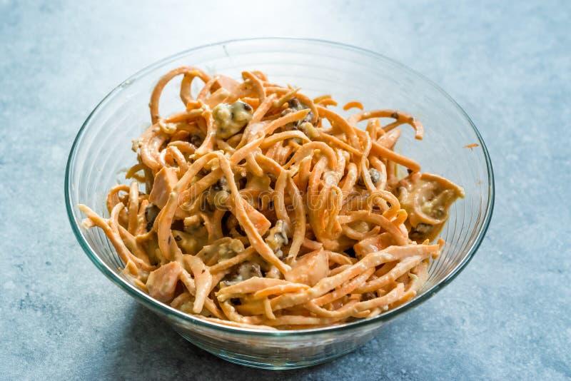 与Tahini/Tahin调味汁、核桃和乳酪的Spiralized未加工的地瓜土豆沙拉在玻璃碗 免版税库存图片
