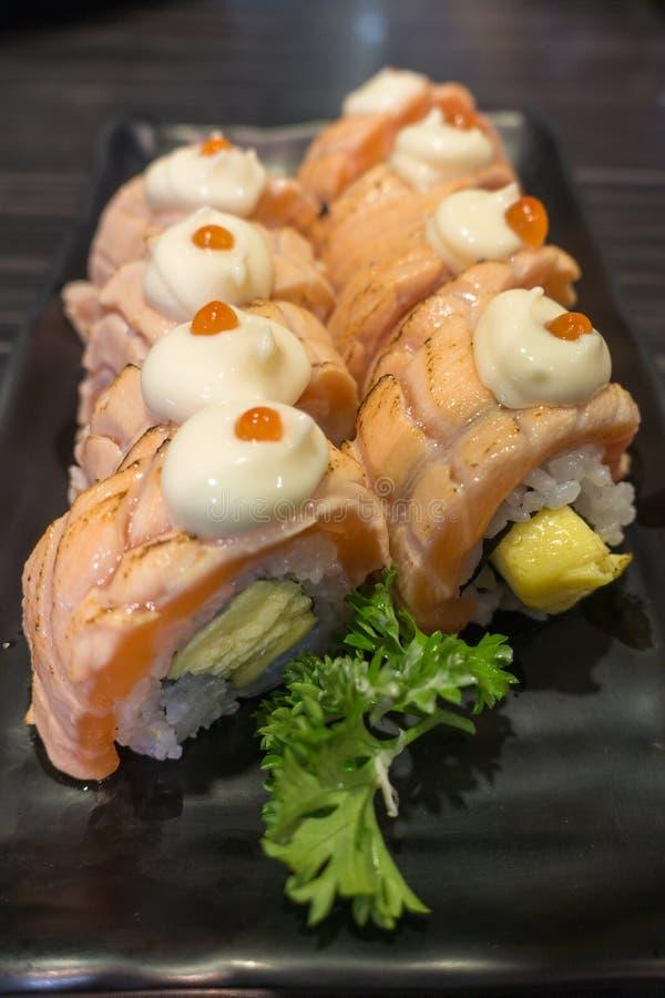 与Tamagoyaki的三文鱼寿司卷在黑陶瓷板材 库存图片