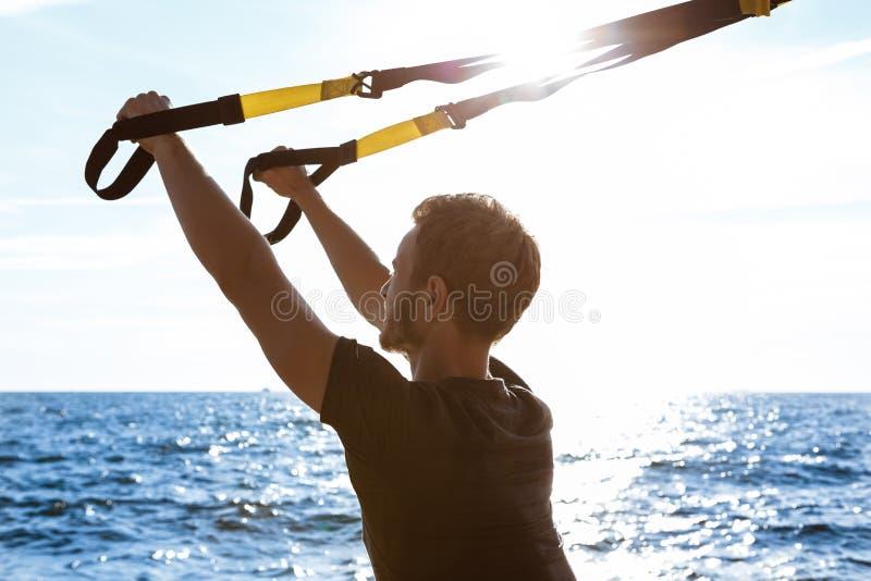与trx的年轻嬉戏人训练在海附近早晨 免版税库存照片