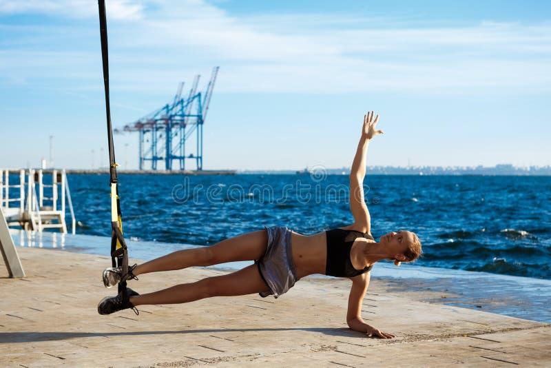 与trx的年轻嬉戏女孩训练在海附近早晨 免版税图库摄影