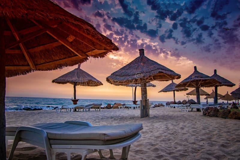 与umrellas的轻便折叠躺椅在与美好的日落的海滩在塞内加尔,非洲 有天空蔚蓝和金黄和红色太阳 ?? 库存图片