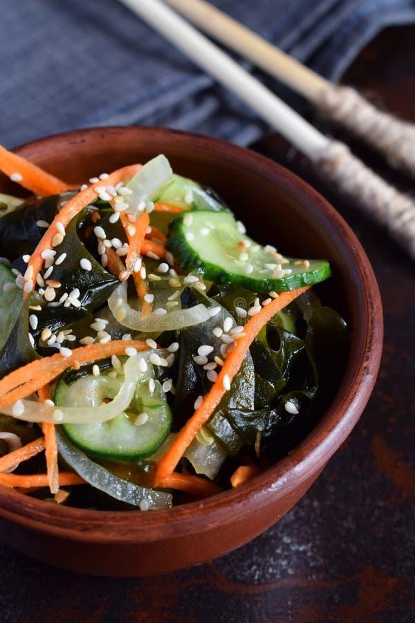 与wakame、黄瓜、葱和红萝卜的日本沙拉sunomono洒了芝麻和筷子 亚洲未加工的食物 免版税库存照片