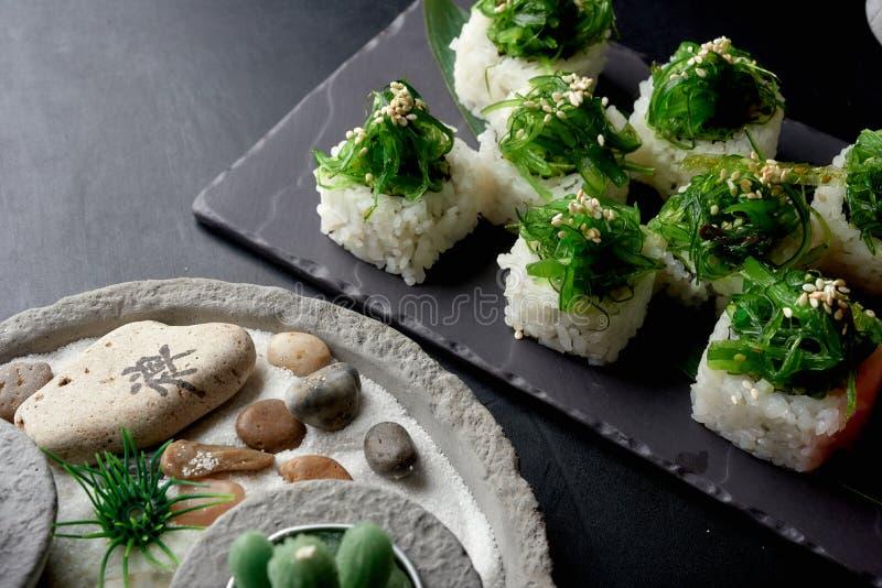 与wakame的健康寿司卷在黑暗的石桌上的上面 免版税图库摄影