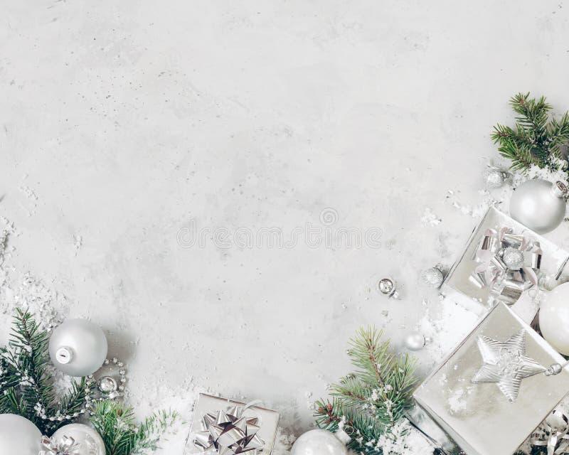 与xmas装饰的圣诞节背景 银色圣诞礼物、杉树分支和中看不中用的物品装饰品在灰色石桌上 平面 库存图片