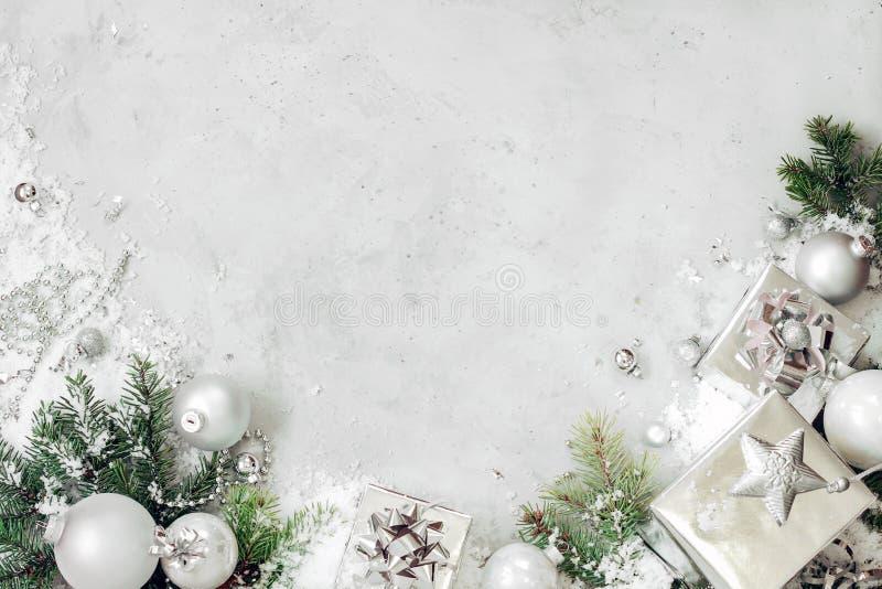 与xmas装饰的圣诞节背景 银色圣诞礼物礼物盒、杉树分支和中看不中用的物品装饰品在灰色石头 免版税库存照片