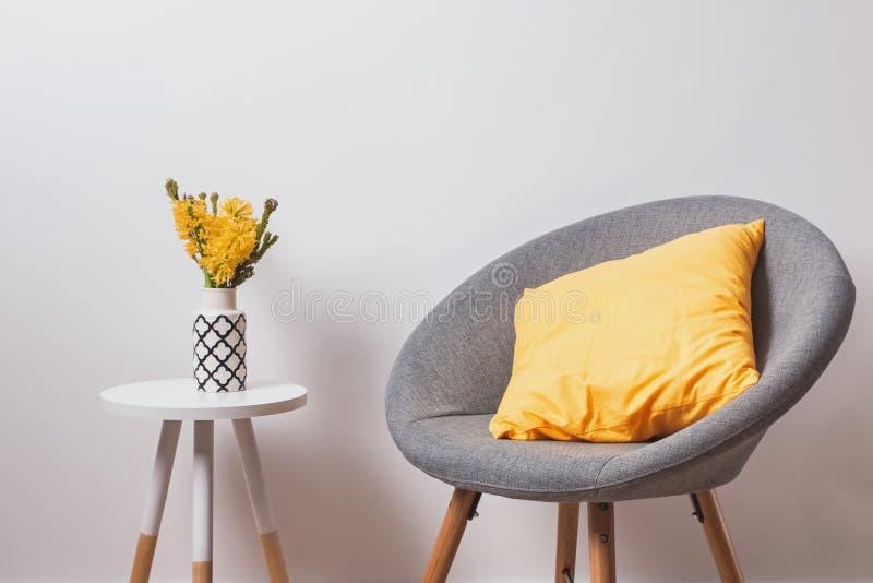 与yekllow枕头和花的舒适灰色椅子在站立在白色墙壁附近的花瓶 免版税库存图片